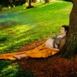 Pregnant woman against tree - Stock Photo