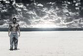 Bodybuilder op strand — Stockfoto