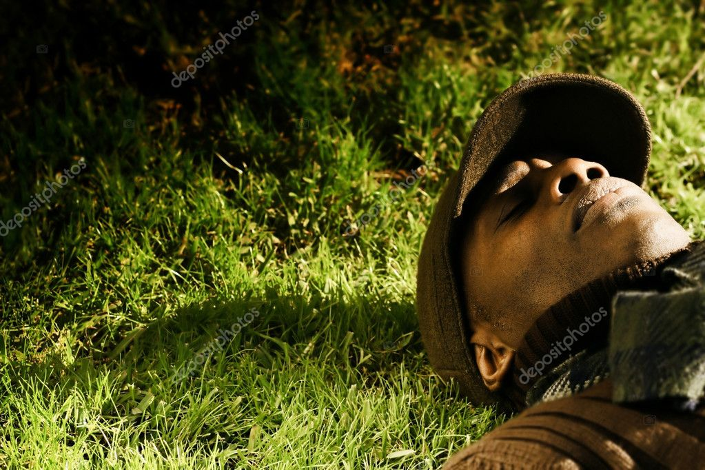 Horizontal portrait of African-American male model laying in the grass with hat  Stock Photo #8470358
