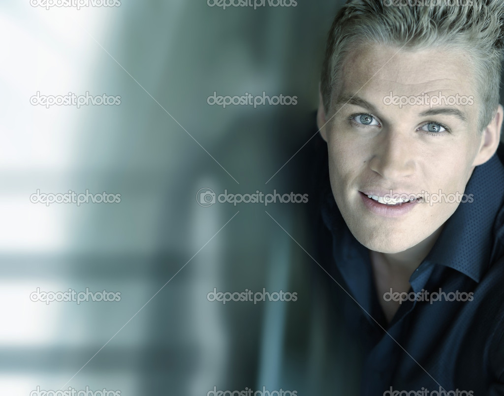 Horizontal close-up portrait of a smiling confident young male model with a futuristic modern background with lots of copy space — Stock Photo #8470472