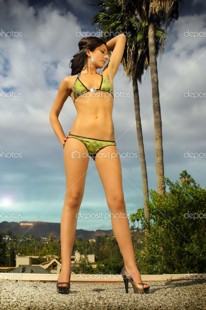 Full body portrait of a young female model in a green bikini and high heels against sky and palm trees — Stock Photo #8470488