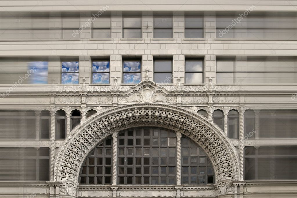 Horizontal architectural stylized detail of the facade of an old building with clouds reflecting in windows — Stock Photo #8470502