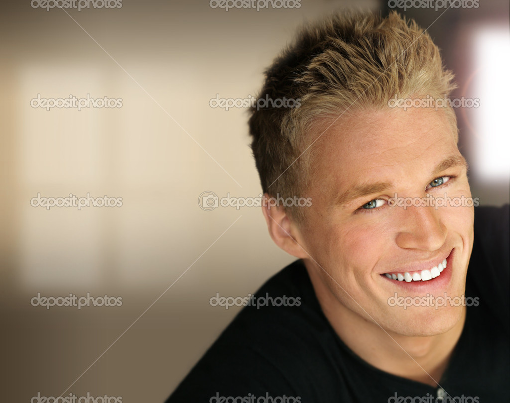 Closeup portrait of a handsome young happy business man with studio lights and modern background  Stock Photo #8501654
