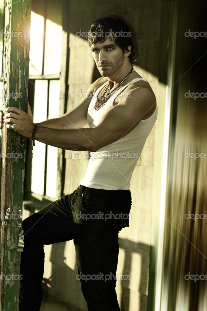 Portrait of a sexy man in white tank top and jeans — Stock Photo #8502401