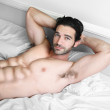 Sexy male model smile in bed — Stock Photo