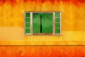 Green window on yellow wall — Stock Photo