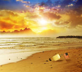 Flag in bottle on beach with sunset — Stock Photo