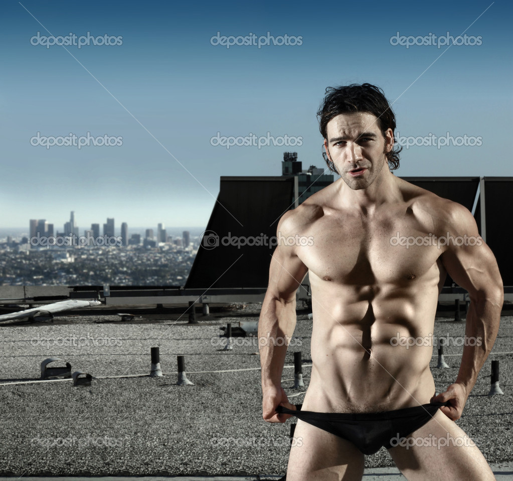 Fashion portrait of sexy male model in black briefs on top of roof with city in background — Stock Photo #8511984