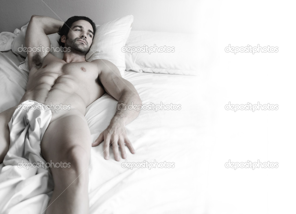 Beautiful young nude muscular male model alone in bed with lots of white copy space  Stock Photo #8512969