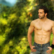Foto Stock: Hunky model with ripped body and ocean behind