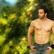 Hunky model with ripped body and ocean behind — Stock Photo