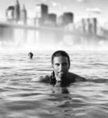 Man in ocean with city background — Stock Photo