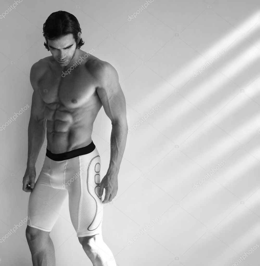 Sexy black and white portrait of young muscular male fitness model in underwear with window light streaming in — Stock Photo #8521712