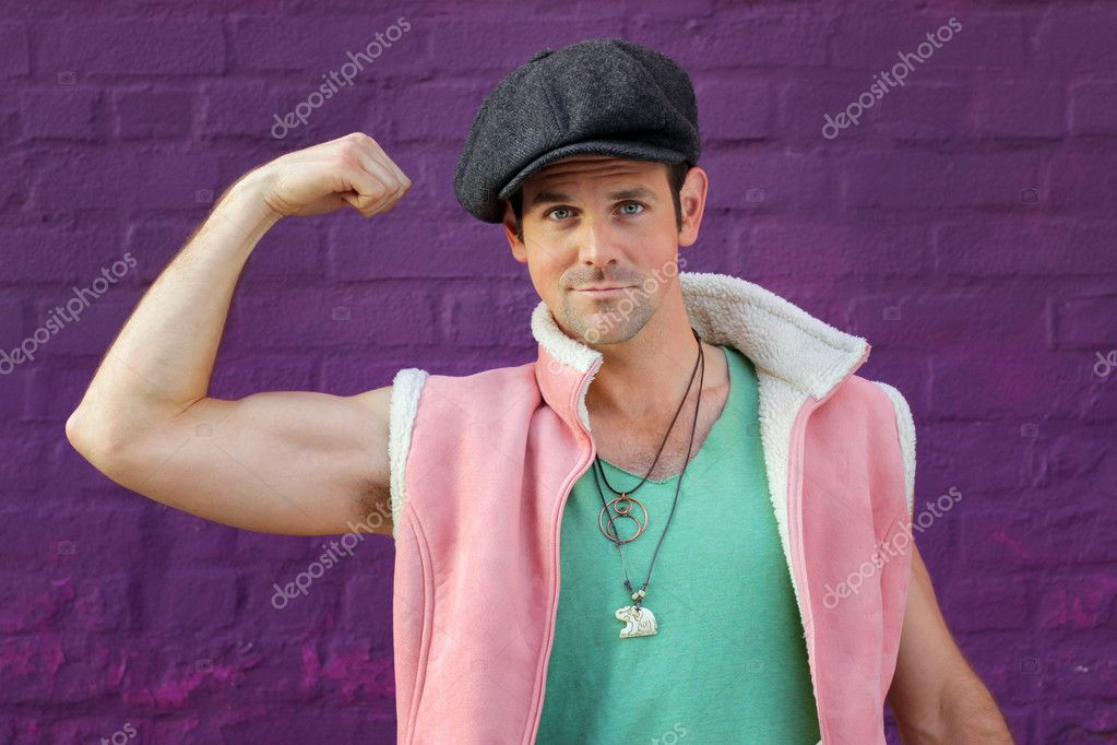 Portrait of a funny man in green vest, hat, and pink tank flexing his muscle against a vibrant wall — Stock Photo #8813373