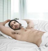 Man in bed — Stockfoto
