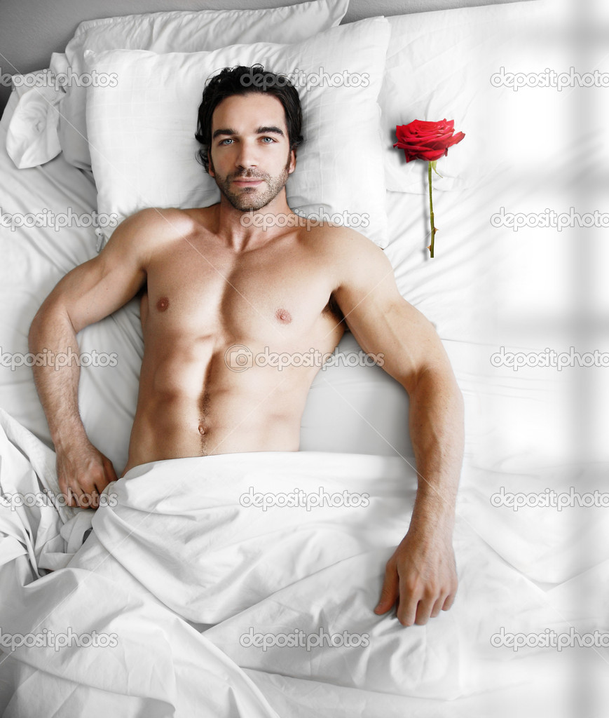 Portrait of a sexy muscular male model waiting in modern bed with single red rose on pillow  Stock Photo #9023323