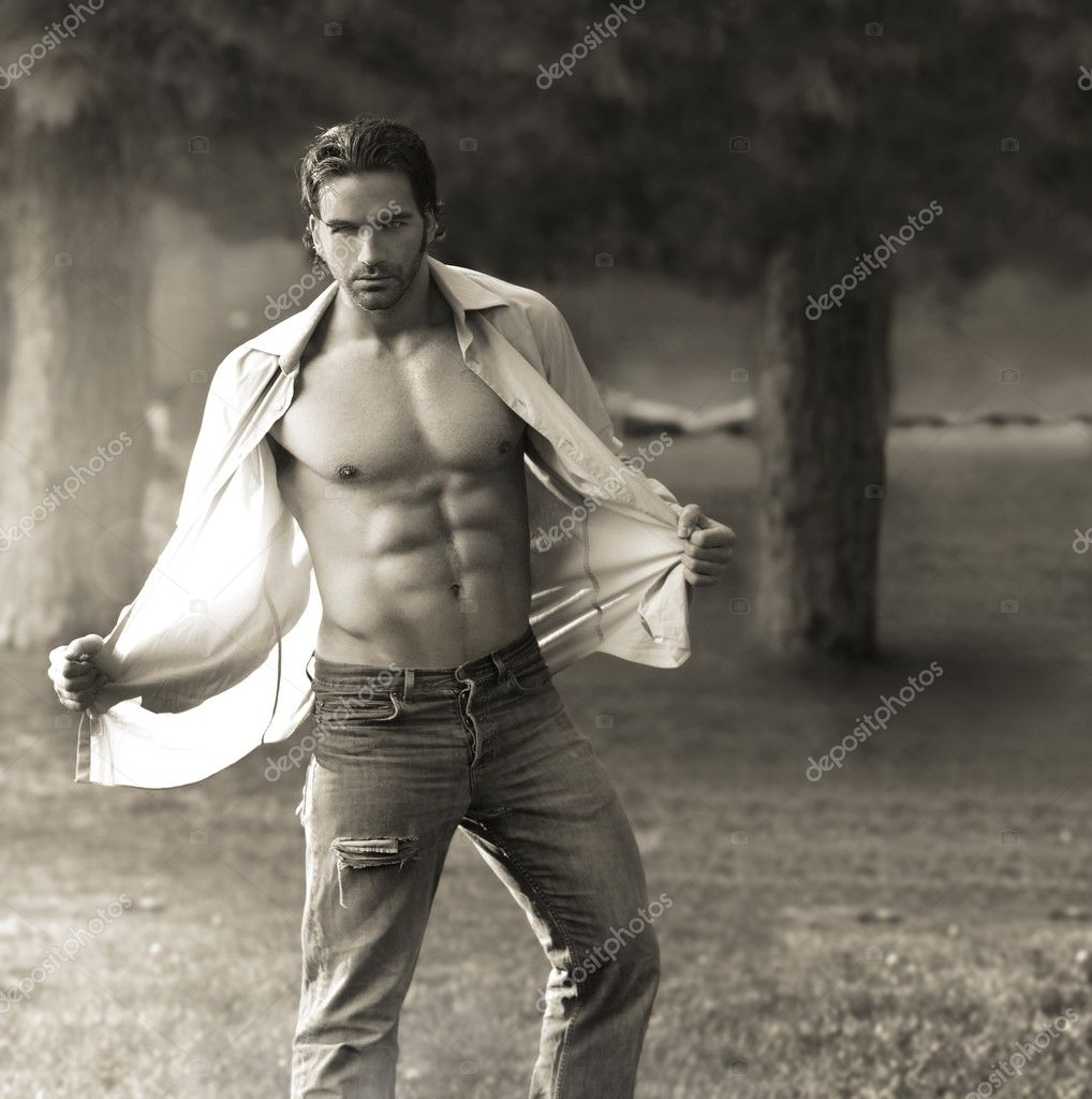 Classic portrait of muscular man outdoors opening his shirt — Stock Photo #9290997