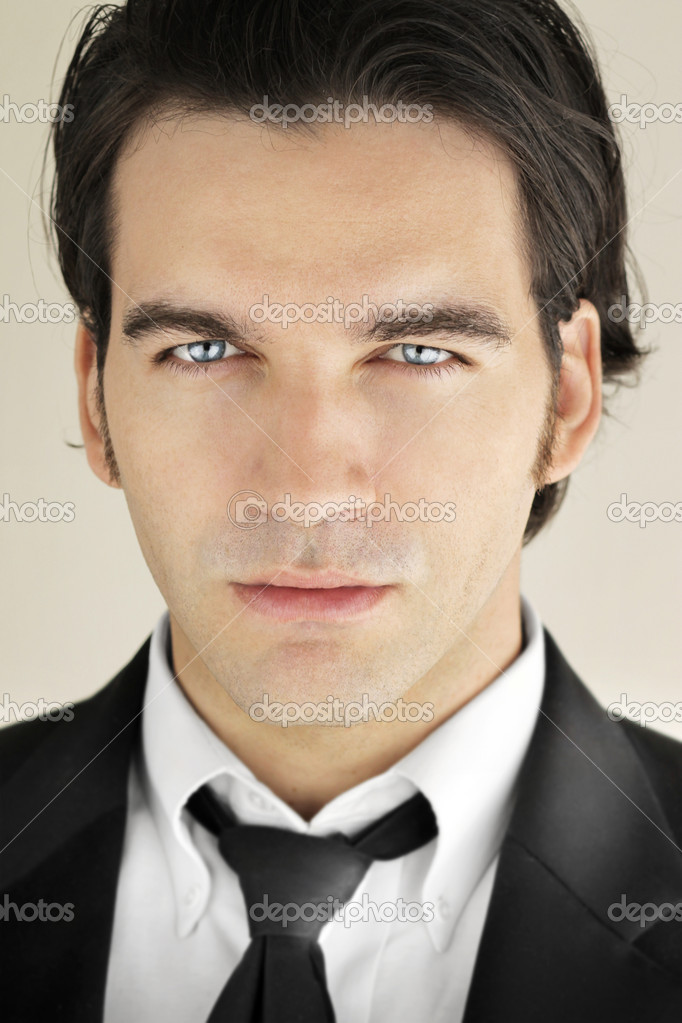 Detailed close-up portrait of a great looking male model in formal black suit and tie with bright blue eyes — Stock Photo #9388394