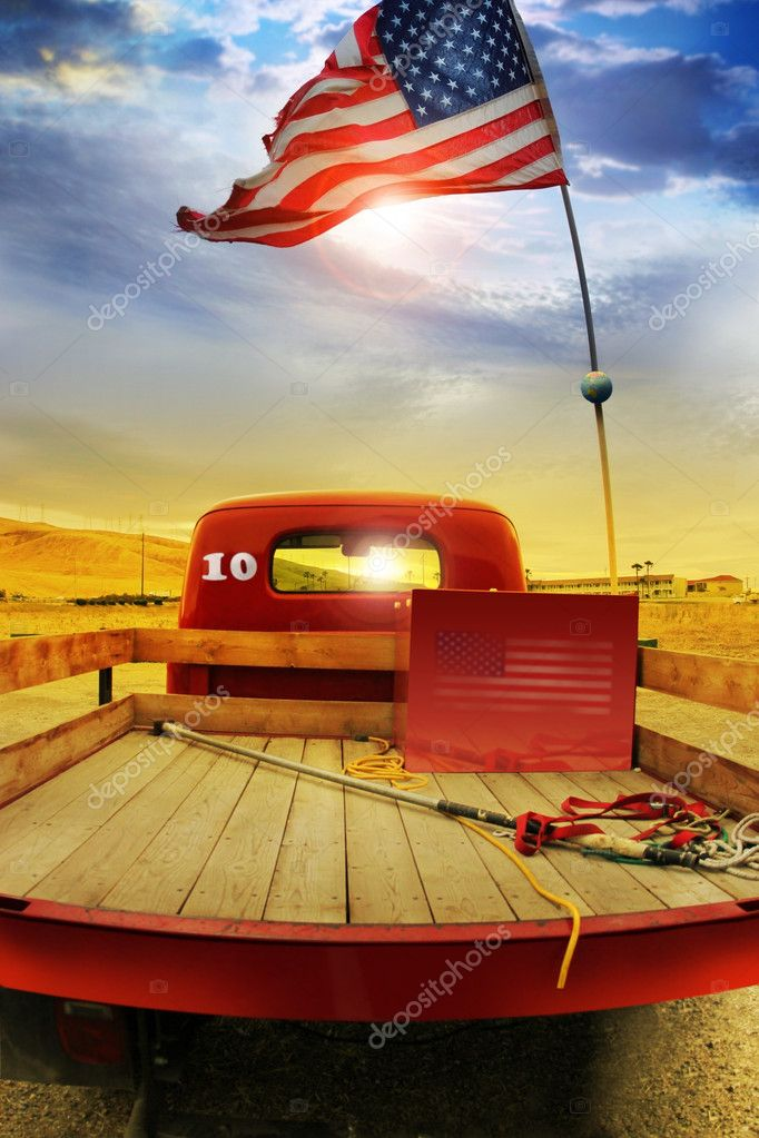 Concept photo of a vintage red vintage pick up truck with American flag waving above against rural dramatic cloudscape  Stock Photo #9393286