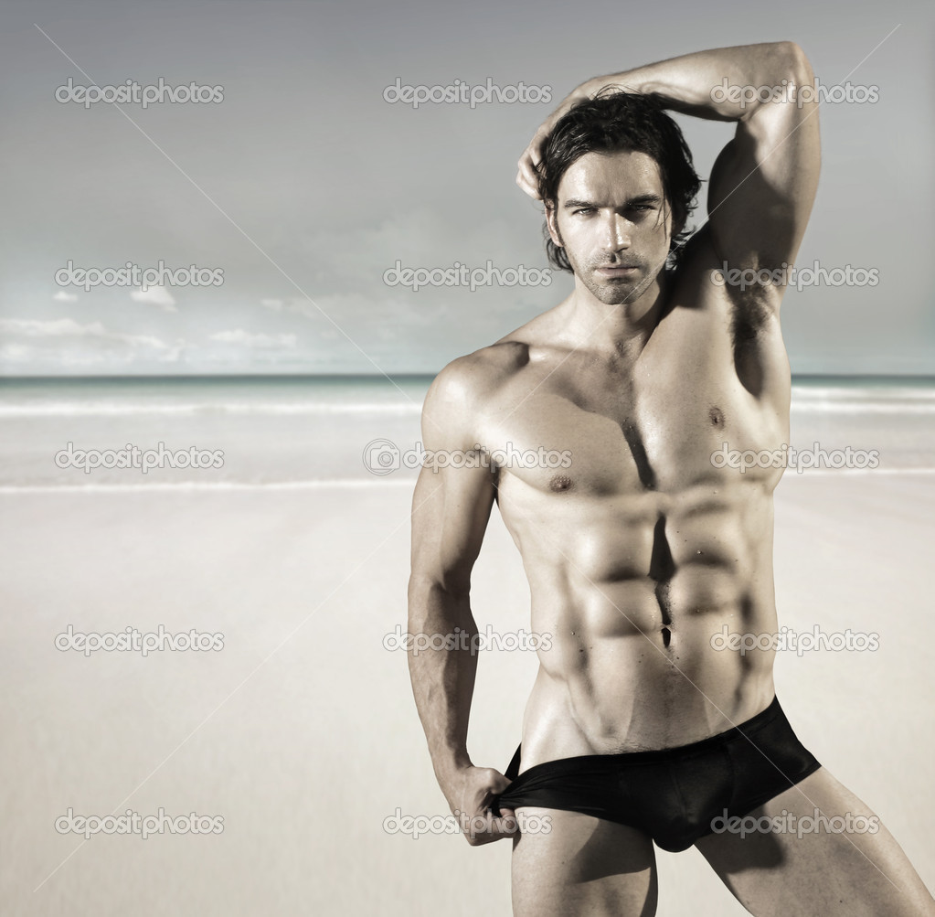 Sexy portrait of a hot buff male fitness model pulling at his bikini briefs on the beach  Foto de Stock   #9572103