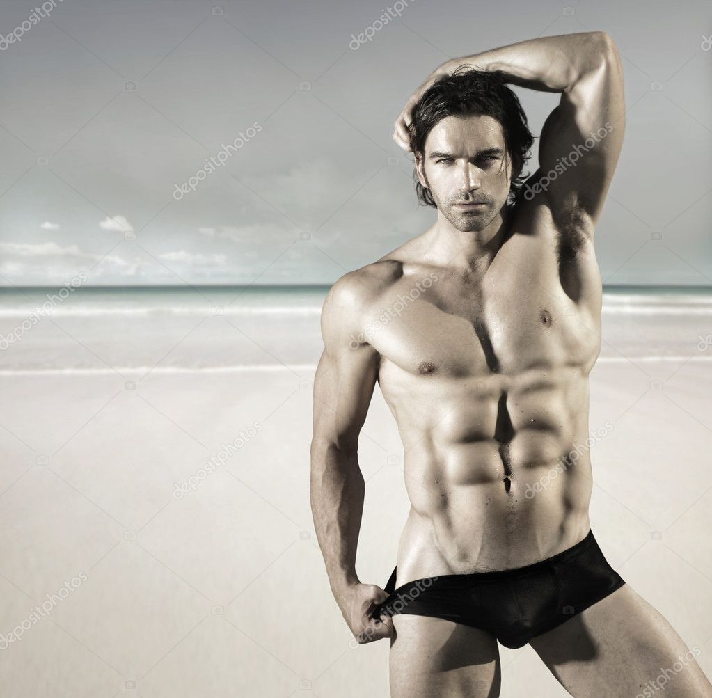Sexy portrait of a hot buff male fitness model pulling at his bikini briefs on the beach — Foto Stock #9572103