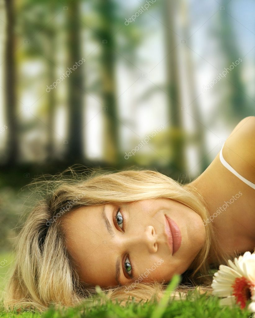 Beautiful serene woman laying in the grass with flower — Stok fotoğraf #9678127