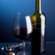 A glass of red wine with bottles on a blue background — Stock Photo
