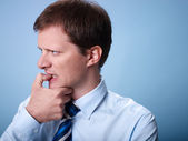 Nervous business man biting finger nails — Stok fotoğraf