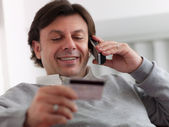 Adult man shopping from home with telephone and credit card — Stock Photo