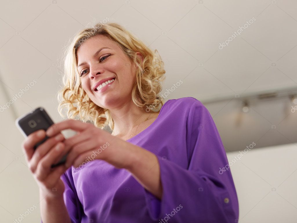 Young beautiful caucasian blonde woman typing e-mail message on smartphone and laughing. Low angle view, copy space — Stock Photo #10302797