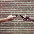 Man and woman using cellphones to share files — ストック写真