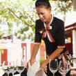 Asian waitress setting table in restaurant - Stok fotoğraf