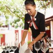 Asian waitress setting table in restaurant - Stock Photo