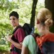 Stock Photo: Couple with backpack doing trekking in wood