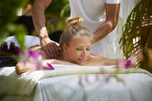 Happy young woman smiling during massage in spa — Stock Photo