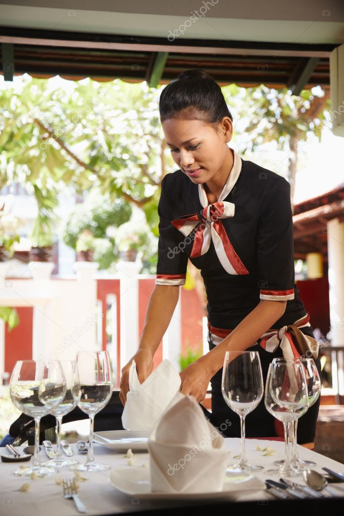 Attractive young woman working as waitress in exclusive restaurant, setting up a table. Waist up, side view — Stock Photo #8402586