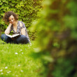 Stock Photo: Young woman reading book in park