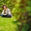 Stock Photo: Young womreading book in park