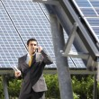 Businessman and solar panels — Stock Photo