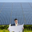 Businessman standing near solar panels — Stock Photo #9301247