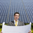 Businessman standing near solar panels — Stock Photo