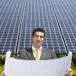 Businessman standing near solar panels — Stock Photo #9301253
