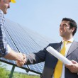 Businessman and electrician shaking hands - Stock Photo
