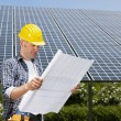 Electrician standing near solar panels - Stock Photo