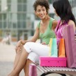 Friends sitting on bench with shopping bags — Stock fotografie