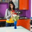 Stock Photo: Womarranging flowers in pot