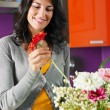 Woman arranging flowers in pot - Foto Stock