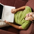 Woman with pc laughing on sofa — Stock Photo