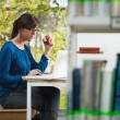 Girl holding apple in library — Stock Photo #9303335