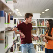 Students flirting in library - Stok fotoğraf